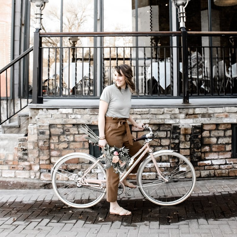 Girl on beautiful dusty pink Shinola bike with bouquet of flowers in hand
