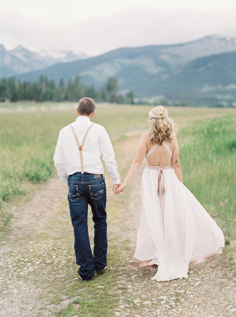 bride and groom walking toward mountains