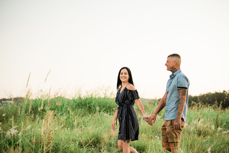 couple-man-women-walking-in-long-grassy-field-at-sunset-lead-images