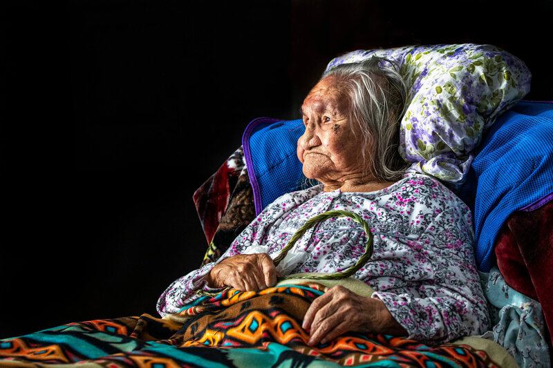 elderly indigenous woman  with sweet grass and blanket