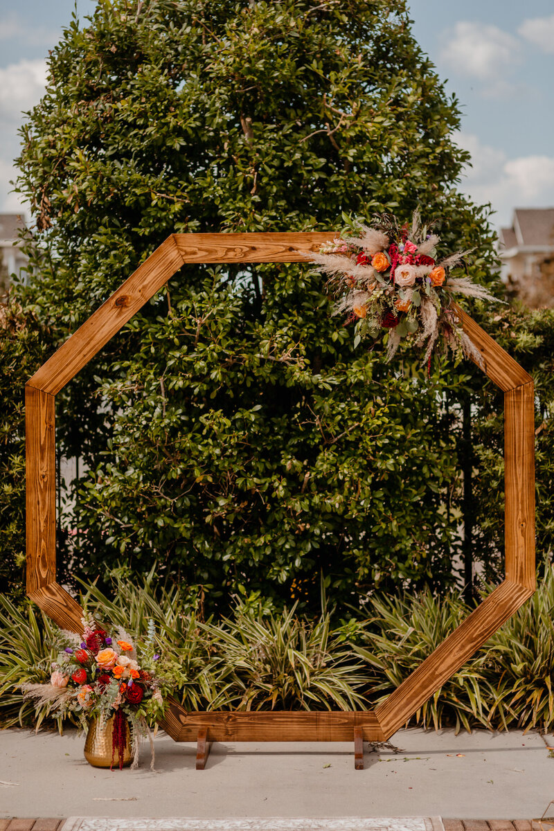 "alt=""flowers on wooden arch outside wedding"""