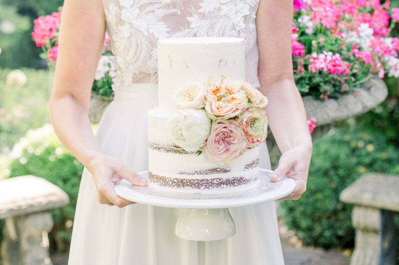 Bride with her small two-tier buttercream wedding cake decorated with flowers and gold flakes for a styled city elopement shoot organized by Lovely & Planned