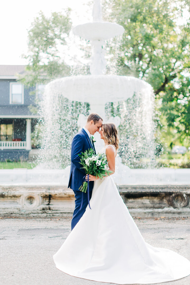 Bride and groom pose for portraits by fountain in Lafayette