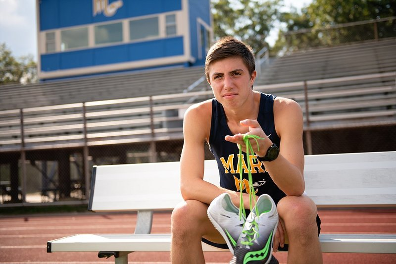 High school senior boy in Mars track uniform seated on bench and holding track shoes at Mars High School track field in Pittsburgh, PA