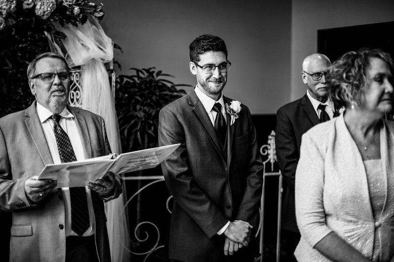 Groom watches his bride walk down the aisle at Sheraton Erie Bayfront Hotel wedding