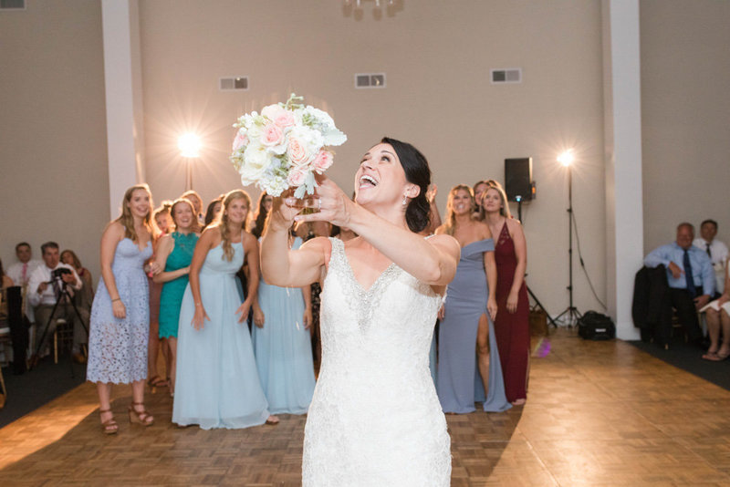 bride throwing bouquet at reception at springfield manor winery and distillery wedding by costola photography
