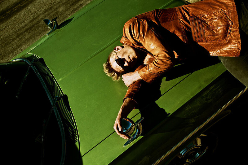 Musician photo Ryan Guldemon lying on hood of green vintage car wearing orange coat and sunglasses Route 66