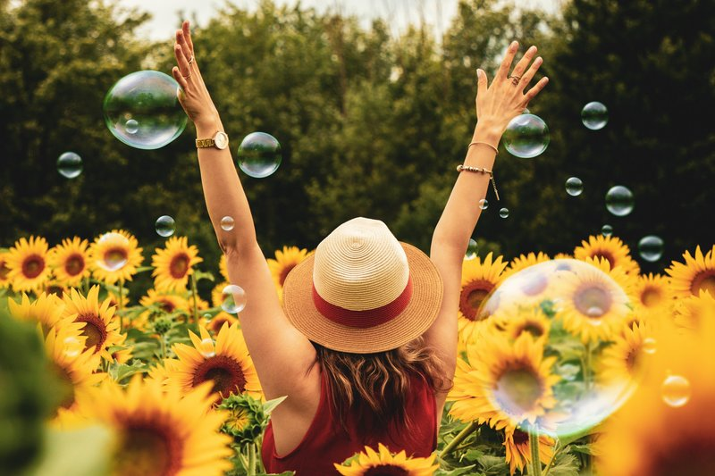 photography-of-woman-surrounded-by-sunflowers-1263986