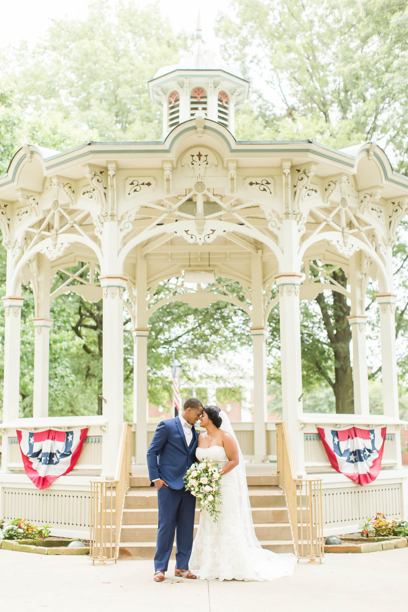 Bride and Groom standing in front of floral arch at Purcell Mansion in Ohio photographed by akron ohio wedding photographer