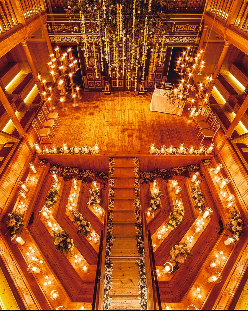 A candlelit  wedding ceremony in a wooden theatre with hanging flowers.