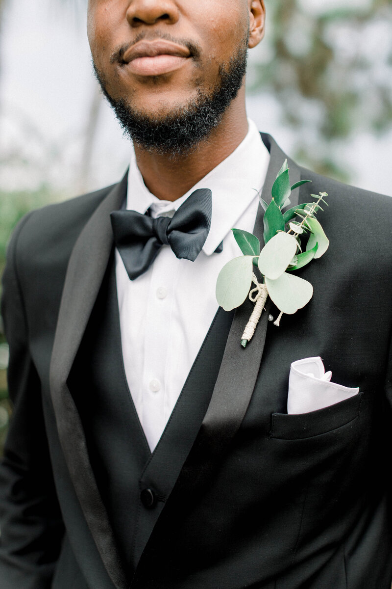 Black groom in black tux from generation tux. Black Bowtie and simple floral boutonniere.