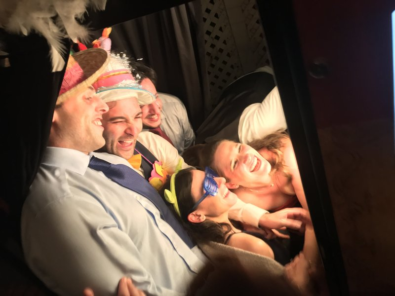 groomsmen and bridesmaids having fun in a photo booth