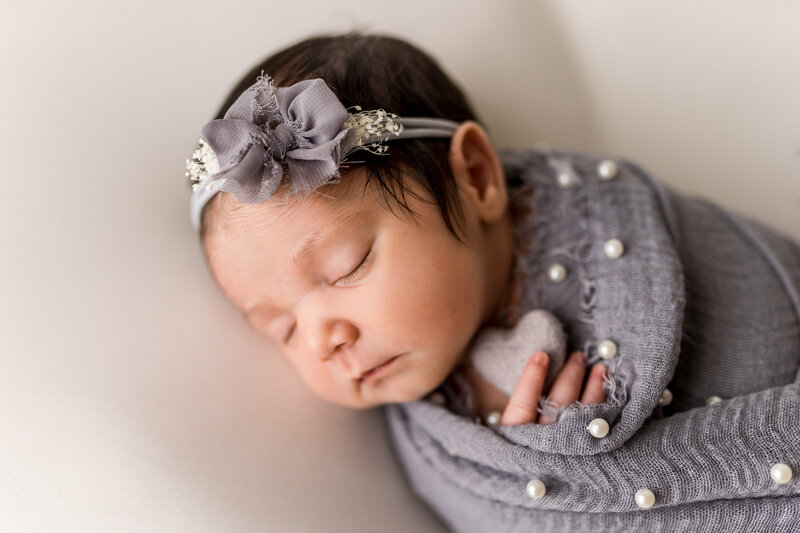 newborn baby girl holding a heart and wearing a headband