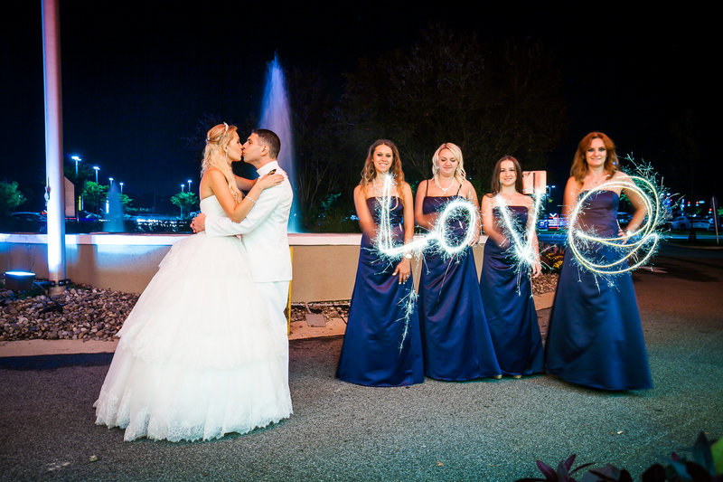 Bride and groom kissing while bridesmaids make  word love with sparklers outside the radisson king of prussia
