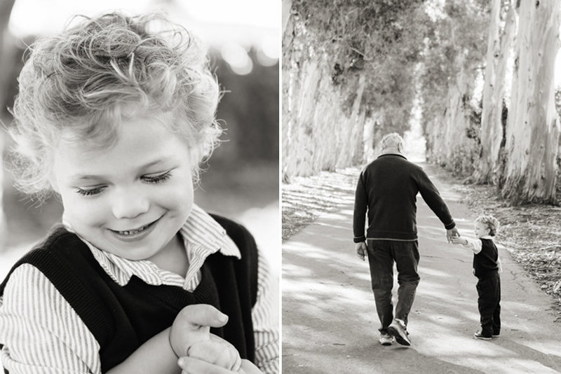 Black and white image of a grandfather holds his grandsons's hand while walking away from the camera