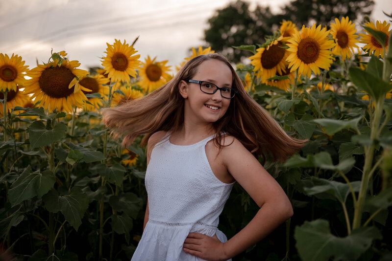 Young girl smiling in sunflower field