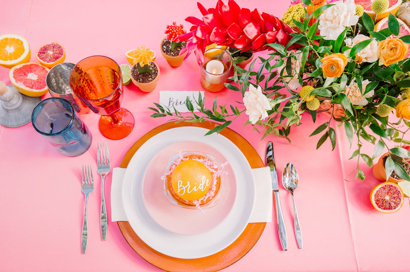 pink head table with tropical floral arrangement and citrus accents