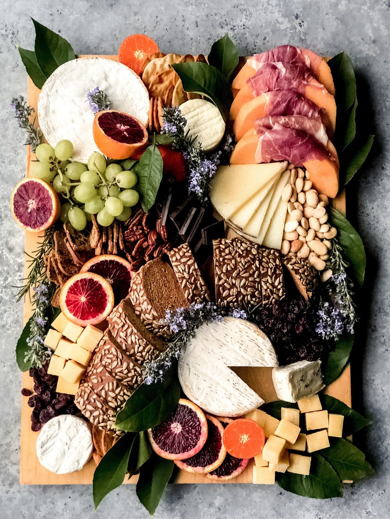 Large cheese board filled with an assortment of cheeses, bread and fresh fruit by Fed & Full Tables & Boards.