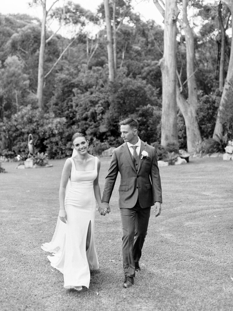 Black and white photo of bride and groom holding hands walking across lawn