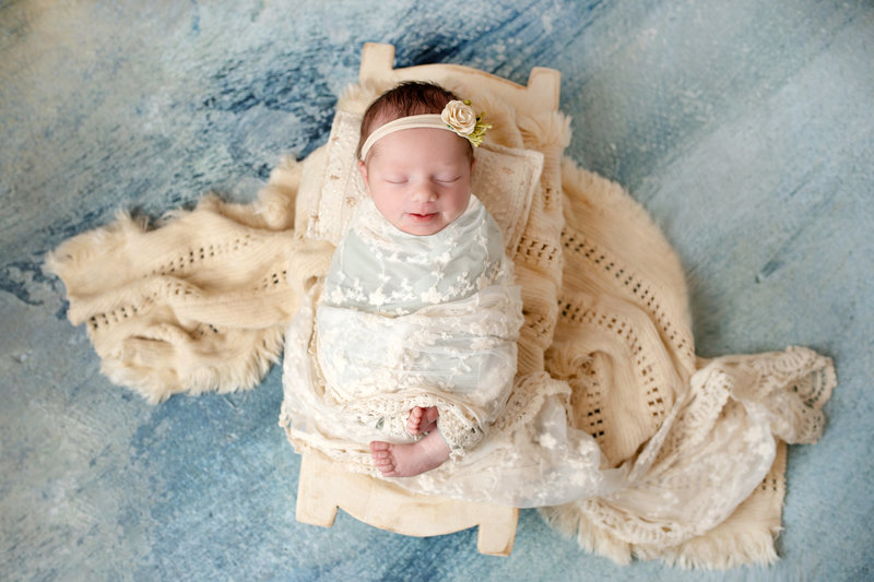 newborn girl swaddled in lace and boho layers in trench on watercolor backdrop