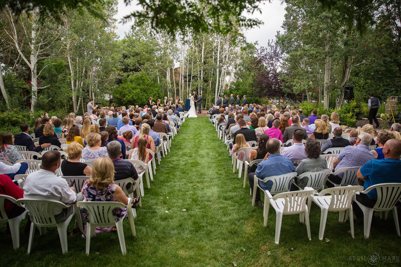 Wedding guests sit in white chairs on the lawn outdoors at Church Ranch Event Center