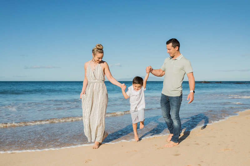 Stacey, Asher, and their son on a sandy Maui beach