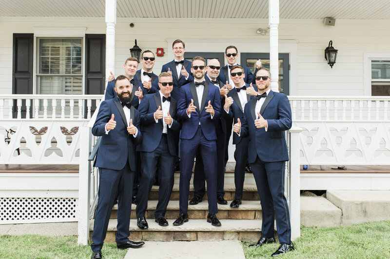 Grooms party smiles wearing sunglasses and thumbs up on historic building steps