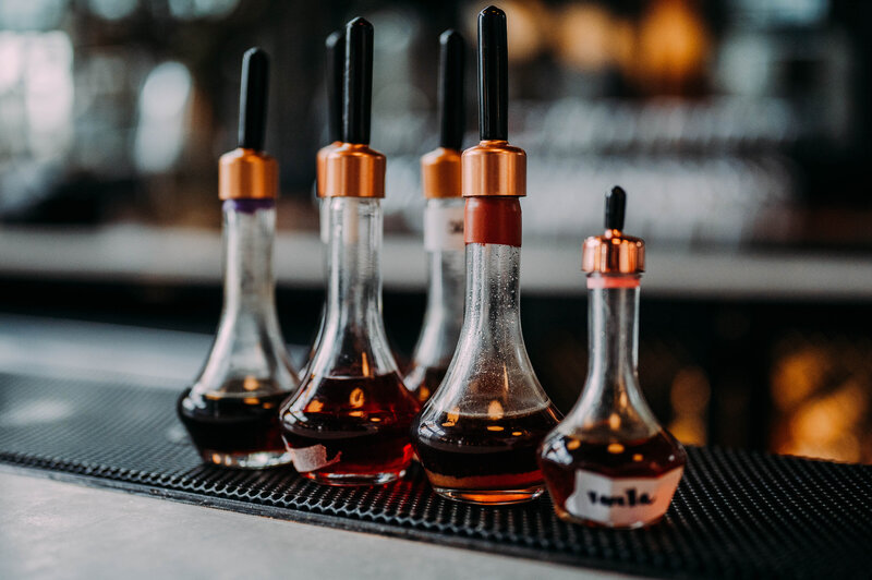 small bottle sit on a bar with bronze caps with an amber liquid inside at philadelphia distilling company shot by philadelphia wedding photographer alex medvick