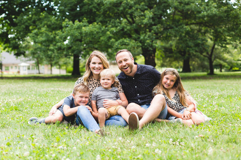 family smiling for portrait while sitting down at park of roses ohio