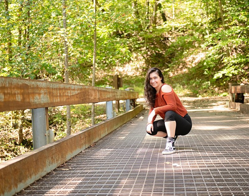 High school senior girl in rust-colored cold shoulder sweater crouching on metal foot bridge at OhioPyle State Park in PA