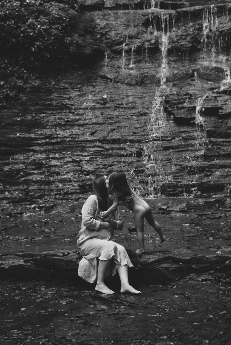 family photographer with daughter at waterfall