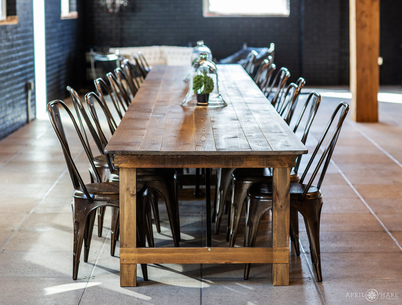 Long wood table with brown metal chairs at Shyft