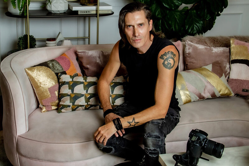 Self portrait of LA based Photographer Mark Maryanovich sitting on sofa with pillows camera on table in front of him