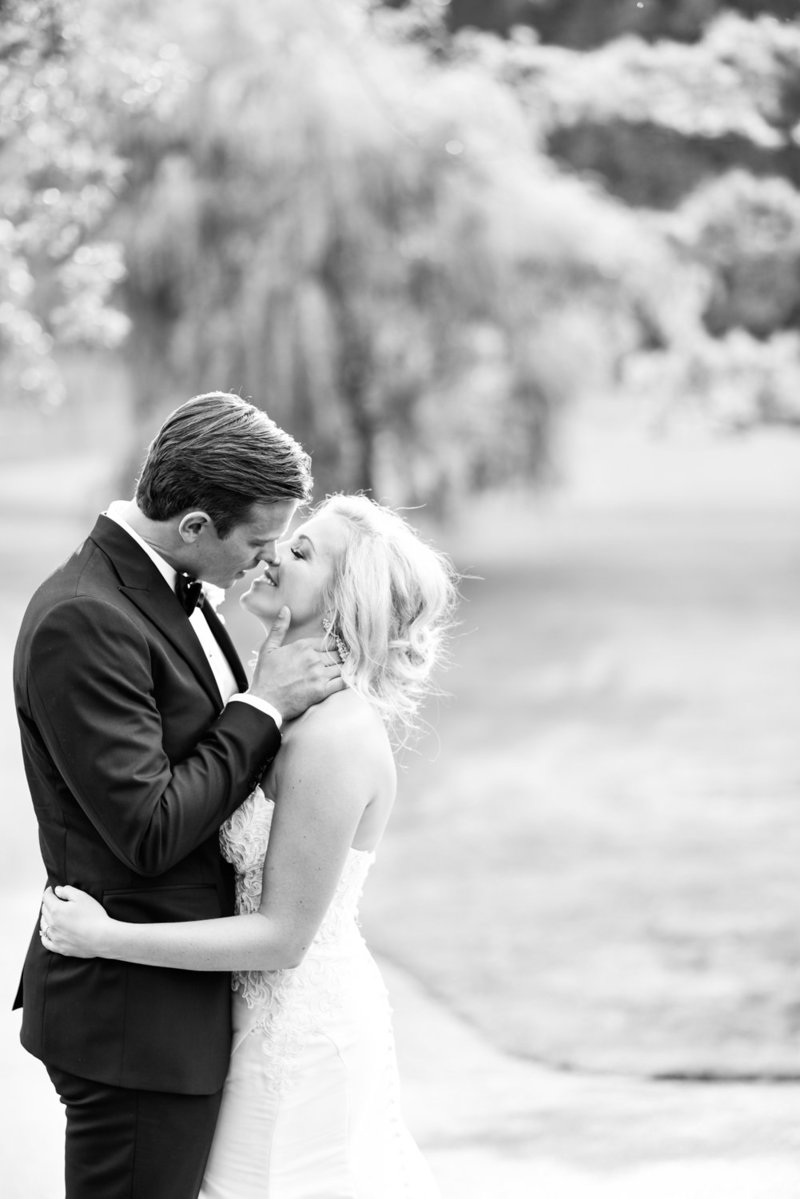 Black and white photo of bride and groom kissing on a golf course
