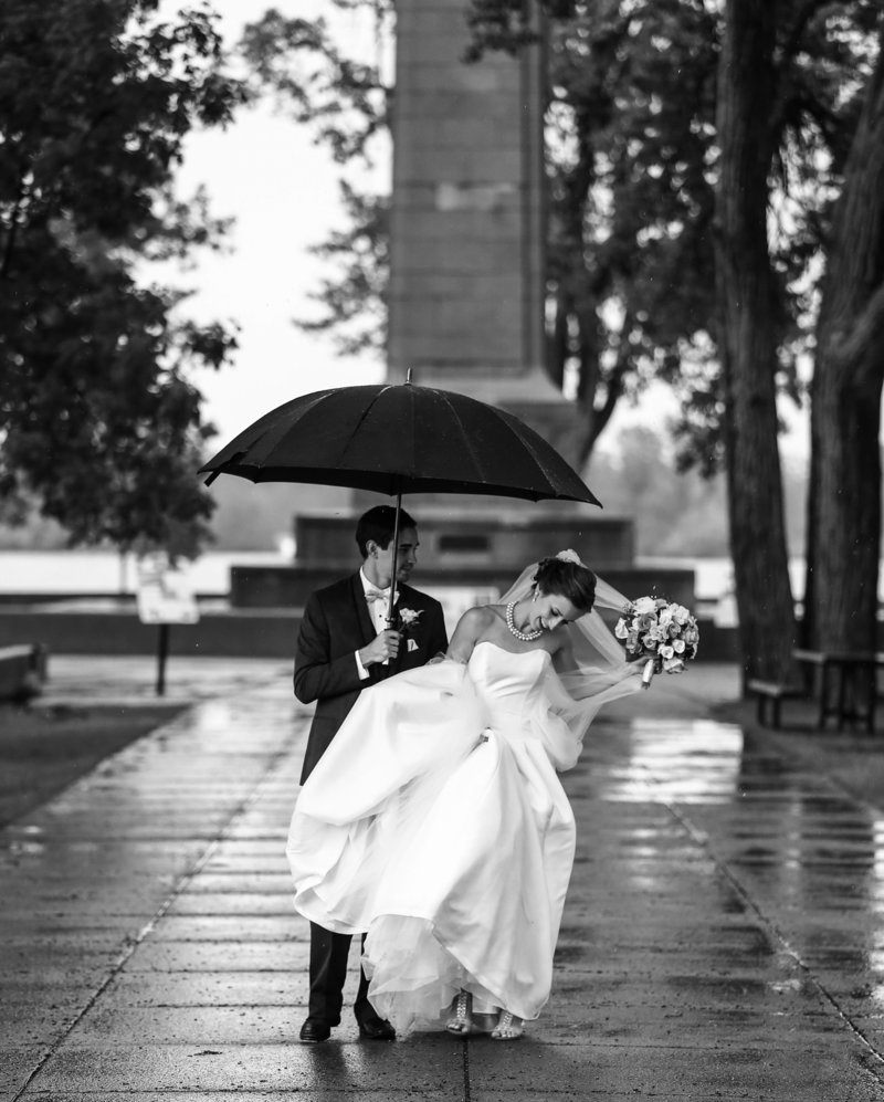 Bride and groom standing under an umbrella in front of Perry Monument at Presque Isle State Park