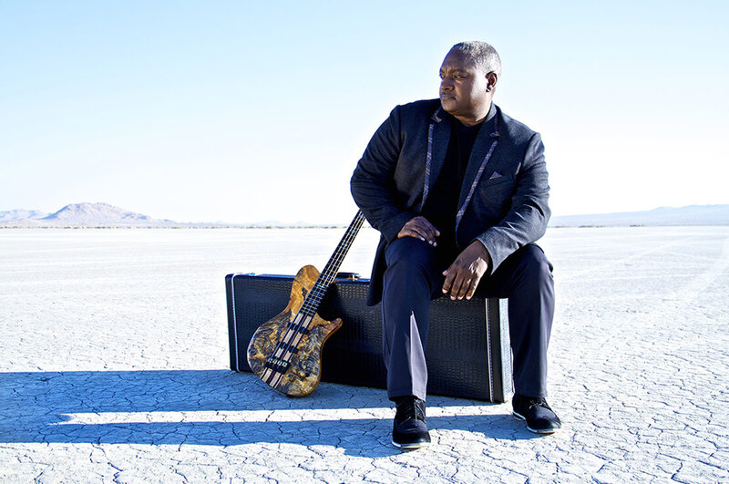 Music portrait Mitchell Coleman Jr sitting on guitar case in desert guitar leaning beside him