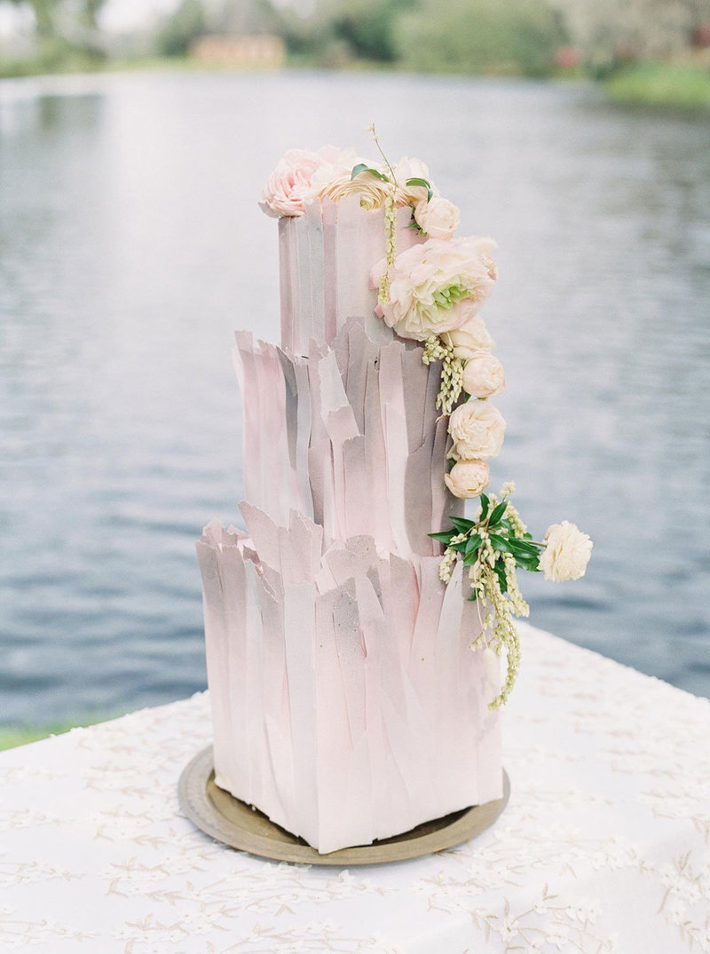 Modern wedding cake on a stand next to a lake at Middleton Place, Charleston