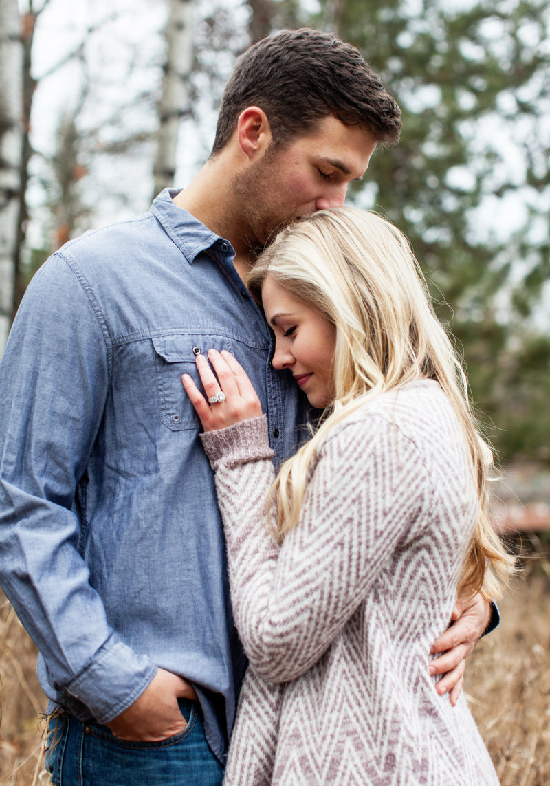 Engaged couple embracing, boy kissing top of girl's head.  Photographer focused on ring.