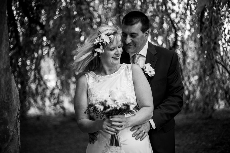 Couple embraces under weeping willow tree at their Schoolhouse wedding in Erie, PA