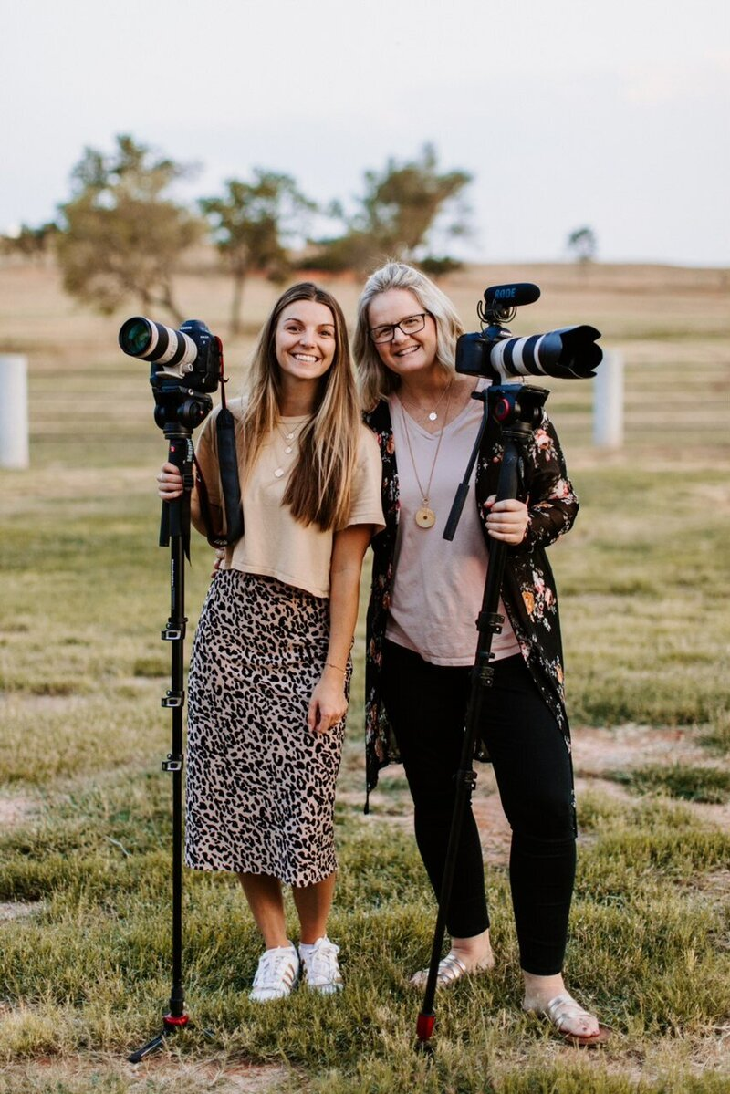 Kaylyn and Dana Pulley holding their cameras smiling at the camera