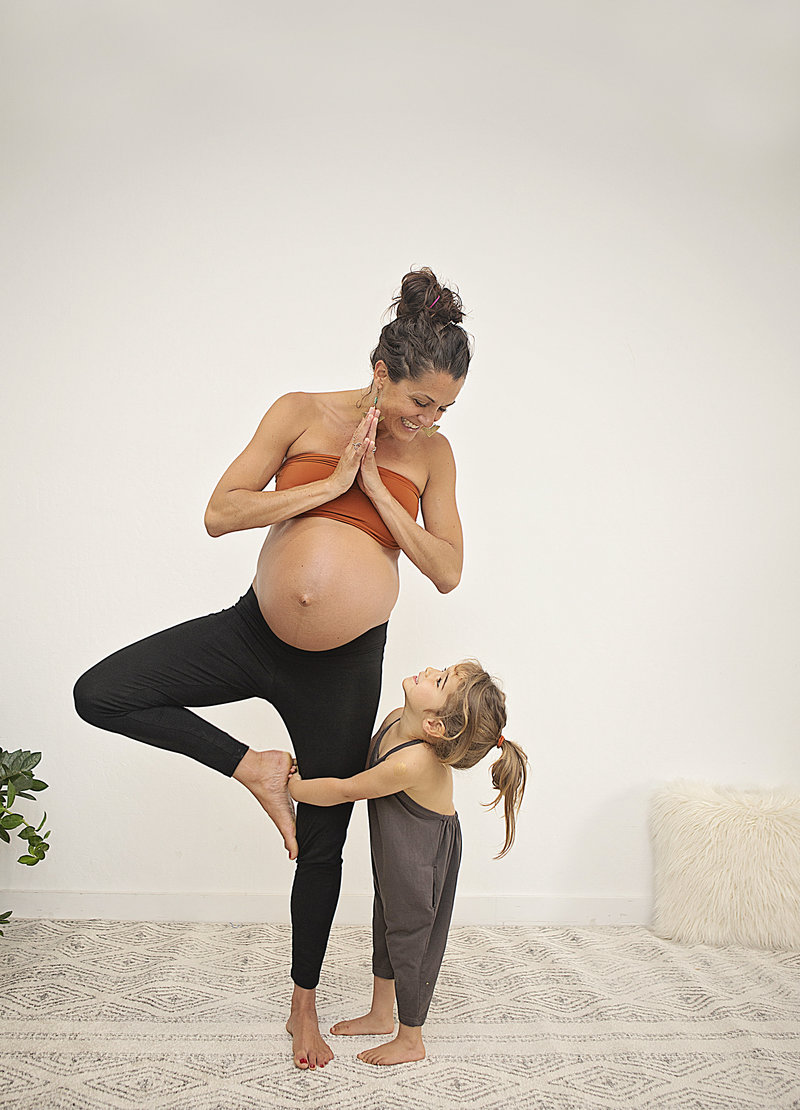 Pregnant yogi mom smiles in tree pose as her toddler daughter holds onto her leg smiling at Hotsource Yoga in Aptos