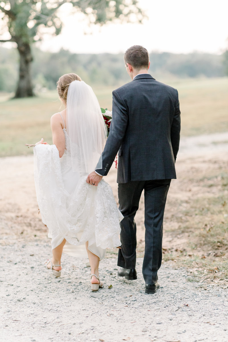 Virginia Wedding Photographer, groom helping hold up bride's dress as they walk through the sand