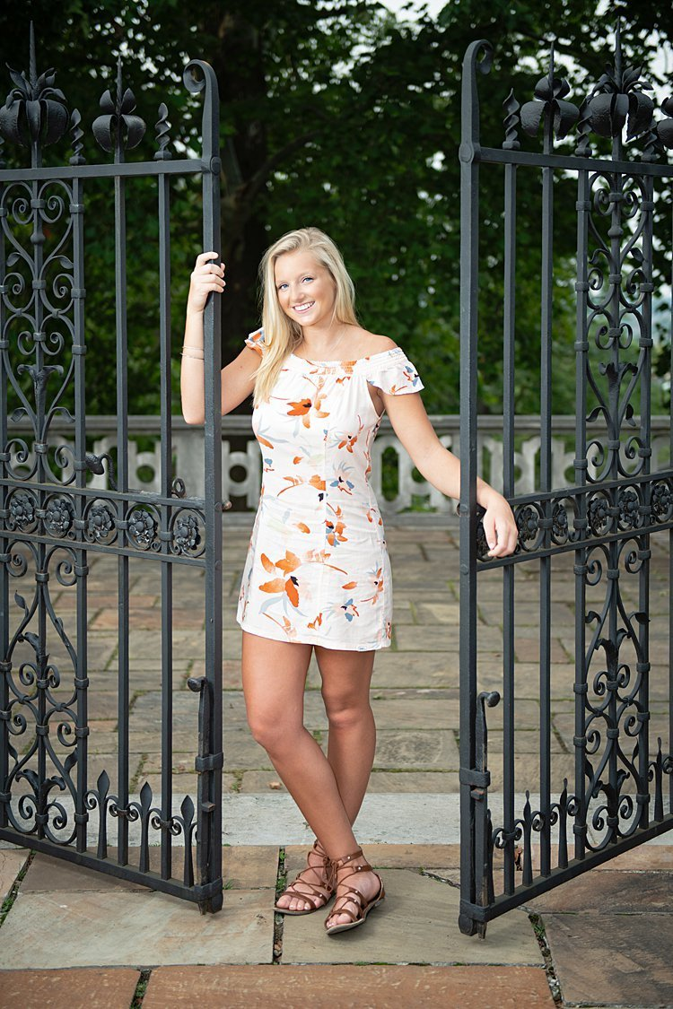 High school senior girl in off the shoulder flowered dress with wrought iron gate at Mellon Park in Pittsburgh, PA