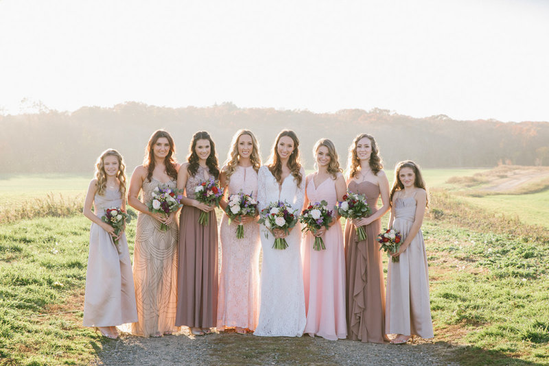 Bridal party wearing blush bridesmaids dresses in magic hour light