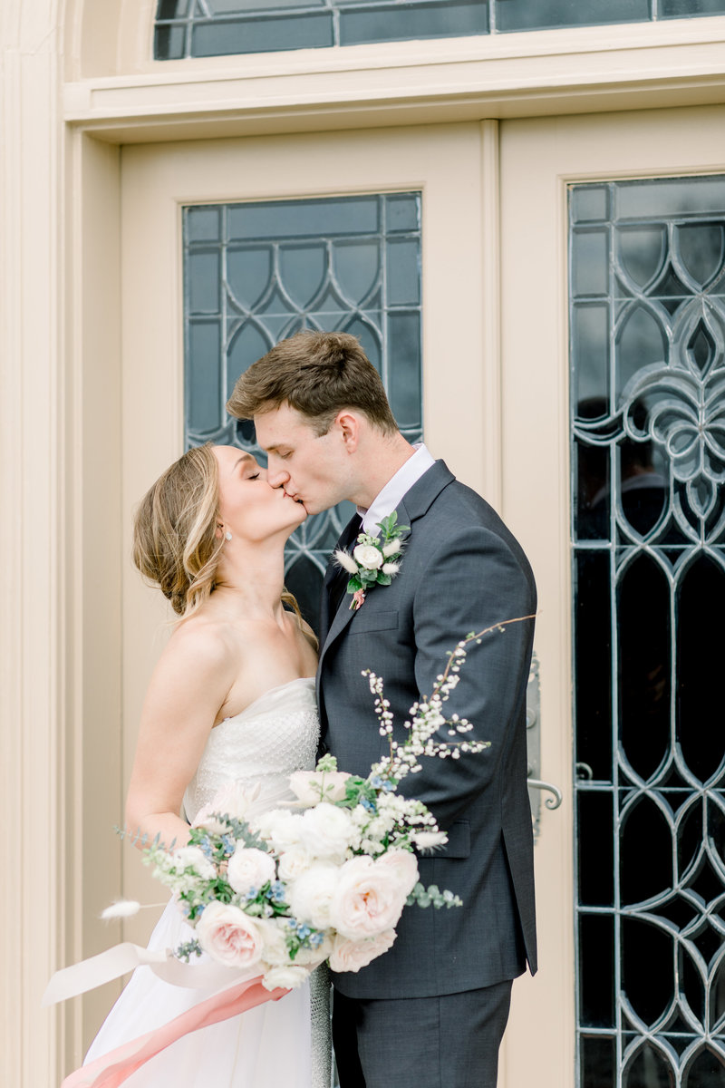 richmond virginia wedding photographer, bride and groom kissing holding wedding florals