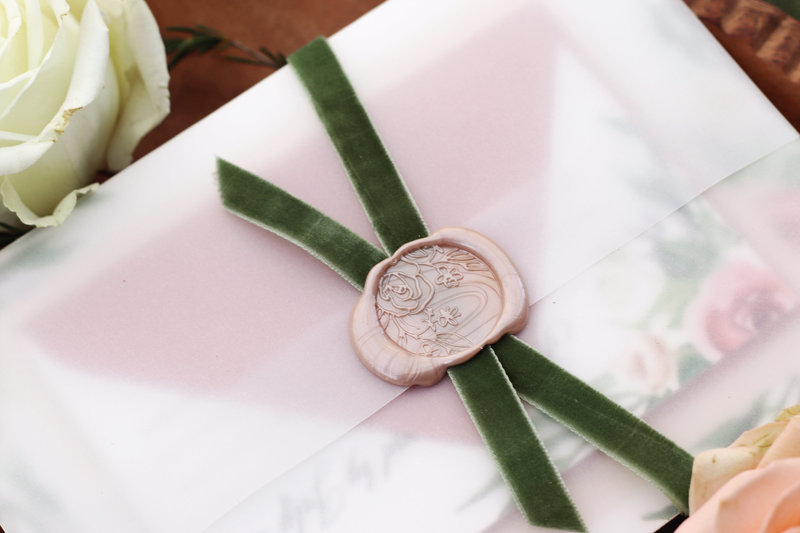 Close up shot: Vellum gate-fold wrap closed with an elegant velvet ribbon and floral wax seal.