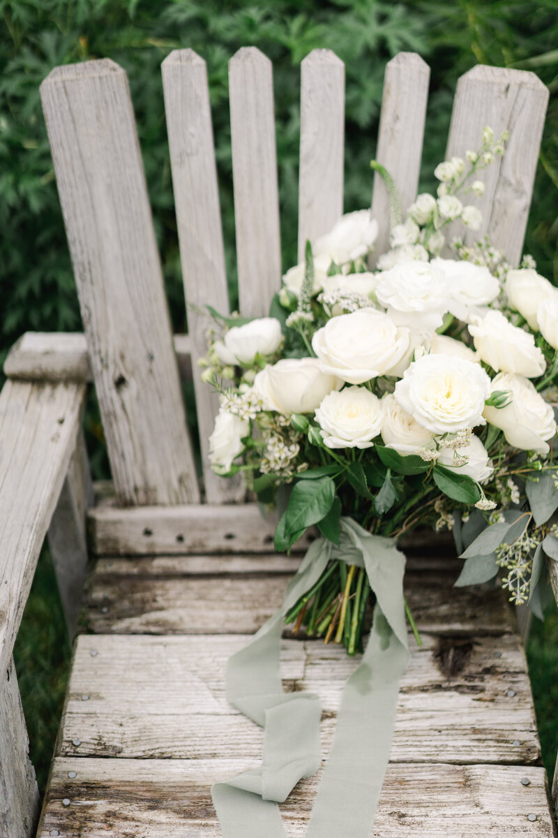 white and green wedding bouquet on wooden bench