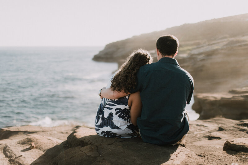 couple-hugging-sitting-on-ocean-cliffside