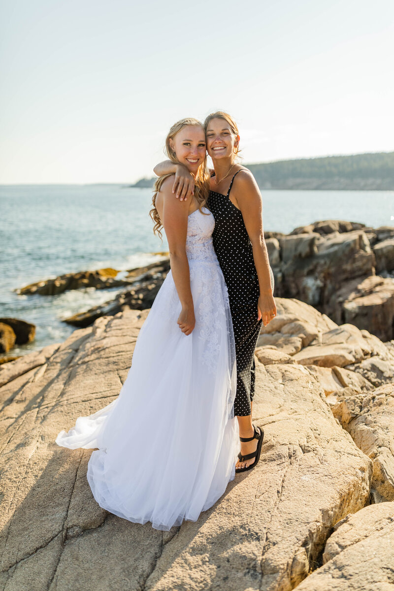 two girls hugging on rocky cliff overlooking water