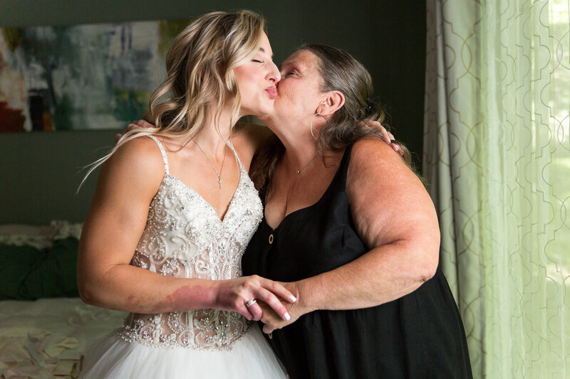 bride and mom kissing